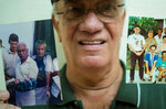 In this April 2, 2018 photo, radio journalist Normando Hernandez Castro, 70, shows pictures with himself with Miguel Mario Diaz-Canel Bermudez in Santa Clara, Cuba. Cuba's President Raul Castro has pledged to step down on Thursday, April 19, and hand the presidency to Diaz-Canel, the man he named in 2013 as his first vice president. (AP Photo/Desmond Boylan)