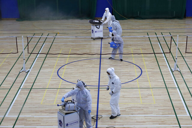 Workers in protective suits spray disinfectant as a precaution against the COVID-19 at an indoor gymnasium in Seoul, South Korea, Tuesday, Feb. 25, 2020. China and South Korea on Tuesday reported more cases of a new viral illness that has been concentrated in North Asia but is causing global worry as clusters grow in the Middle East and Europe. (AP Photo/Lee Jin-man)