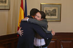 Spain's caretaker Prime Minister Pedro Sanchez, left, and Podemos party leader Pablo Iglesias hug after signing an agreement at the parliament in Madrid, Spain, Tuesday, Nov. 12, 2019.The leaders of Spain's Socialist party and the left-wing United We Can (Podemos) party say they have reached a preliminary agreement toward forming a coalition government. But the deal announced Tuesday won't provide enough votes in parliament for the Socialists, who won a general election, to take office without the support of other parties. (AP Photo/Paul White)
