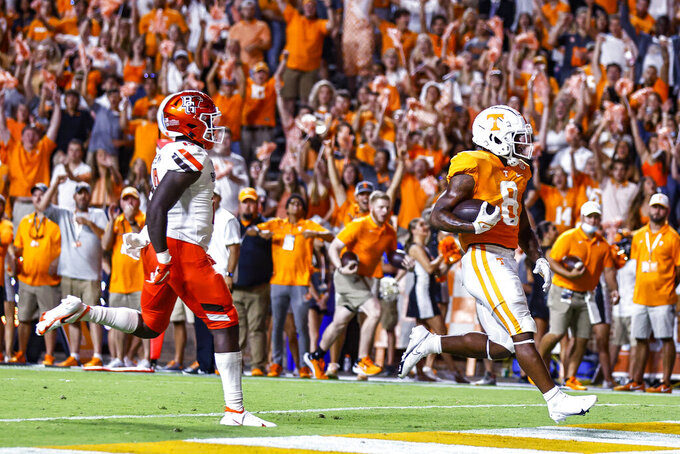 Tennessee running back Tiyon Evans (8) crosses the goal line as Bowling Green linebacker JB Brown (12) gives chase during the second half of an NCAA college football game Thursday, Sept. 2, 2021, in Knoxville, Tenn. (AP Photo/Wade Payne)