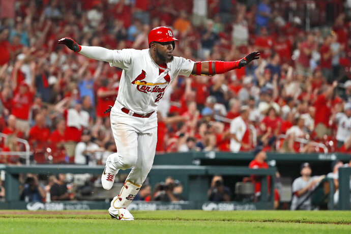 St. Louis Cardinals' Marcell Ozuna celebrates as he runs down the first base line on a ground-rule double that scored two runs during the seventh inning of a baseball game against the Washington Nationals, Monday, Sept. 16, 2019, in St. Louis. (AP Photo/Jeff Roberson)