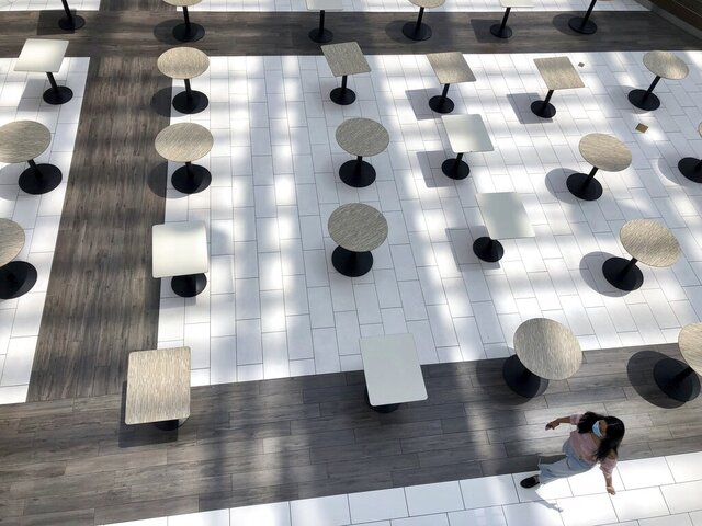 A woman wearing a protective mask walks through the mostly empty food court as Alabama's largest shopping mall, the Riverchase Galleria reopened in Hoover, Ala., Tuesday, May 5, 2020. Dozens of stores, including major retailers, remained closed as the mall opened for business for the first time during the coronavirus pandemic. (AP Photo/Jay Reeves)