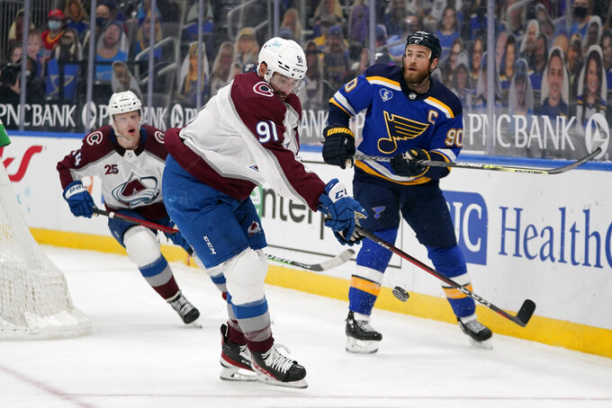 Colorado Avalanche's Nazem Kadri (91) reaches for a loose puck along side teammate Carl Soderberg and St. Louis Blues' Ryan O'Reilly (90) during the third period of an NHL hockey game Thursday, April 22, 2021, in St. Louis. (AP Photo/Jeff Roberson)