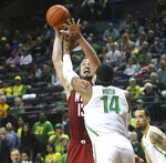 Washington State's Jeff Pollard, left, shoots over Oregon's Kenny Wooten during the second half of an NCAA college basketball game Sunday, Jan 27, 2019, in Eugene, Ore. (AP Photo/Chris Pietsch)