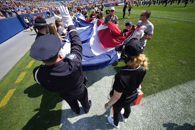 An American flag is rolled out for the playing of the national anthem before the first half of an NCAA college football game between Texas A&M and Colorado, Saturday, Sept. 11, 2021, in Denver. (AP Photo/David Zalubowski)