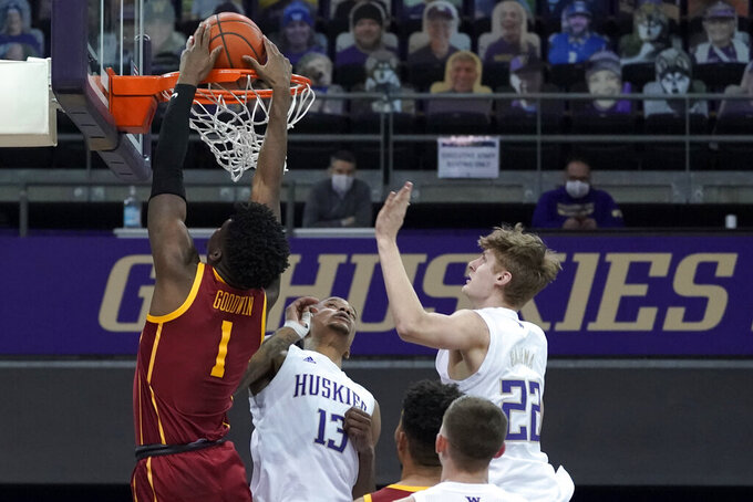 Southern California forward Chevez Goodwin (1) dunks over Washington forward Hameir Wright (13) and guard Cole Bajema (22) during the first half of an NCAA college basketball game Thursday, Feb. 11, 2021, in Seattle. (AP Photo/Ted S. Warren)