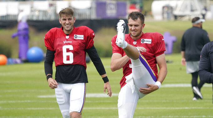 Minnesota Vikings quarterbacks Jake Browning, right, and Danny Etling take part in stretching during an NFL football training camp at TCO Stadium, Tuesday, Aug. 3, 2021, in Eagan, Minn. (AP Photo/Jim Mone)