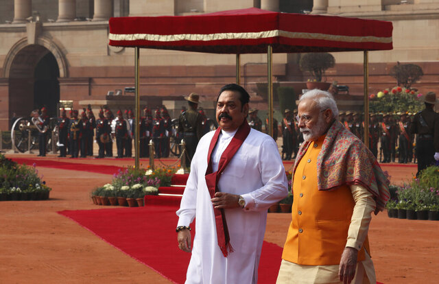 Indian Prime Minister Narender Modi, right, and his Sri Lankan counterpart Mahinda Rajapaksa walk together after a ceremonial reception for Rajapkasa in New Delhi, India, Saturday, Feb. 8, 2020. Rajapaksa is on a four day state visit to India. (AP Photo/Manish Swarup)