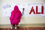 """FILE - Zaina Piracha, 12, writes a message on a banner before an interfaith service at the Islamic Cultural Center of Louisville following the death of Muhammad Ali, in this Sunday, June 5, 2016, file photo. A new documentary looks at the city that raised Muhammad Ali, Louisville, Kentucky, and the week of his funeral, when the community came together to celebrate the legacy of """"The Greatest.""""  (AP Photo/David Goldman, File)"""