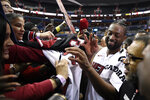 Miami Heat guard Dwyane Wade, right, signs for fans after an NBA basketball game against the Washington Wizards, Saturday, March 23, 2019, in Washington. The Heat won 113-108. (AP Photo/Nick Wass)