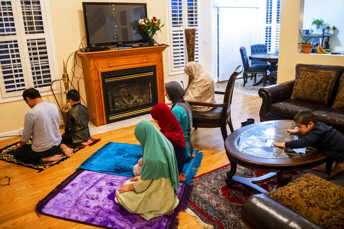 The Ashfaq family during the Maghrib prayer as they observe Ramadan, Tuesday, May 12, 2020, in Center Township. Like most Muslim families during this time, when the pandemic has resulted in mosques shutting down, the Ashfaq family has been observing Ramadan almost entirely at home this year, including their evening Iftar meals to break their daylong fast and their cycle of daily prayers. In past years they would typically go a couple of days per week to their mosque for evening activities. Muslims observe the holy month of Ramadan with daytime fasting and acts of prayer, study and charity. (Michael M. Santiago/Post-Gazette via AP)