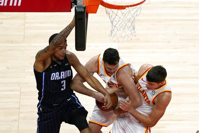Orlando Magic forward Chuma Okeke (3) battles Atlanta Hawks' Danilo Gallinari, center, and Bogdan Bogdanovic, right,for a rebound during the second half of an NBA basketball game Sunday, Dec. 13, 2020, in Atlanta. (AP Photo/John Bazemore)