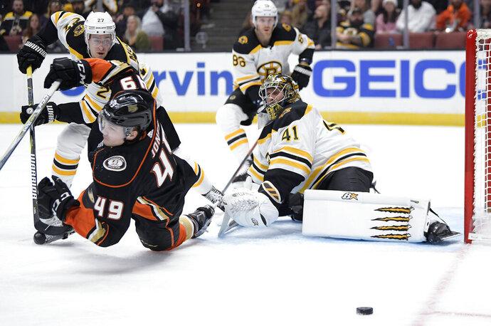 Boston Bruins goaltender Jaroslav Halak, right, deflects a shot as Anaheim Ducks left wing Max Jones, left, falls and defenseman John Moore, back left, and defenseman Kevan Miller watch during the second period of an NHL hockey game Friday, Feb. 15, 2019, in Anaheim, Calif. (AP Photo/Mark J. Terrill)