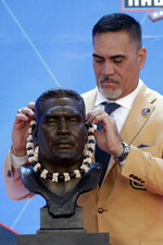 Former NFL player Kevin Mawae puts a lei on a bust of himself during the induction ceremony at the Pro Football Hall of Fame, Saturday, Aug. 3, 2019, in Canton, Ohio. (AP Photo/Ron Schwane)