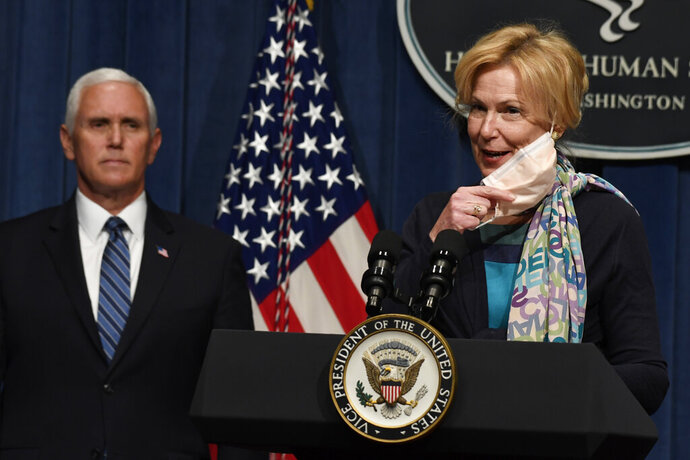 Dr. Deborah Birx, right, takes off her mask as she goes to speak during a news conference with members of the Coronavirus Task Force at the Department of Health and Human Services in Washington, Friday, June 26, 2020. Vice President Mike Pence listens at left. (AP Photo/Susan Walsh)