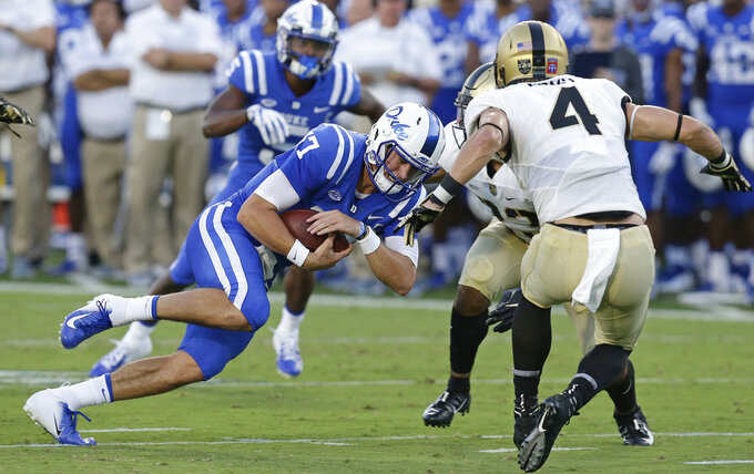 Duke quarterback Daniel Jones (17) runs the ball while Army's Max Regan (4) looks for the tackle during the first half of an NCAA college football game in Durham, N.C., Friday, Aug. 31, 2018. (AP Photo/Gerry Broome)