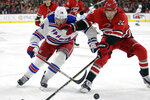 New York Rangers center Greg McKegg (14) and Carolina Hurricanes defenseman Brett Pesce (22) skate to the puck during the first period of an NHL hockey game in Raleigh, N.C., Thursday, Nov. 7, 2019. (AP Photo/Gerry Broome)