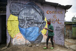 FILE - In this Saturday, April 18, 2020 file photo, a boy wearing a face mask carries a small bowl of