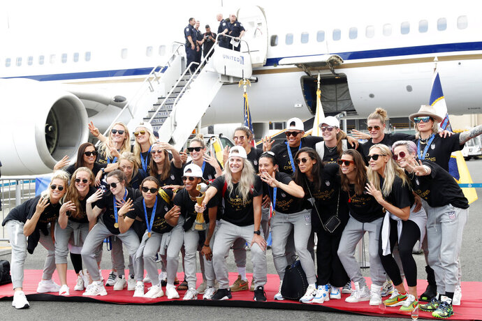 Members of the United States women's soccer team, winners of a fourth Women's World Cup, pose with the trophy by their plane after arriving at Newark Liberty International Airport, Monday, July 8, 2019, in Newark, N.J. Julie Ertz holds the trophy, Megan Rapinoe, front right, gestures, and Alex Morgan, back left, also gestures. (AP Photo/Kathy Willens)