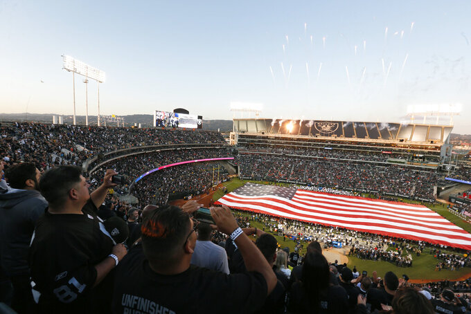 Fans stand for the National Anthem at RingCentral Coliseum before the start of an NFL football game between the Oakland Raiders and the Denver Broncos Monday, Sept. 9, 2019, in Oakland, Calif. (AP Photo/D. Ross Cameron)