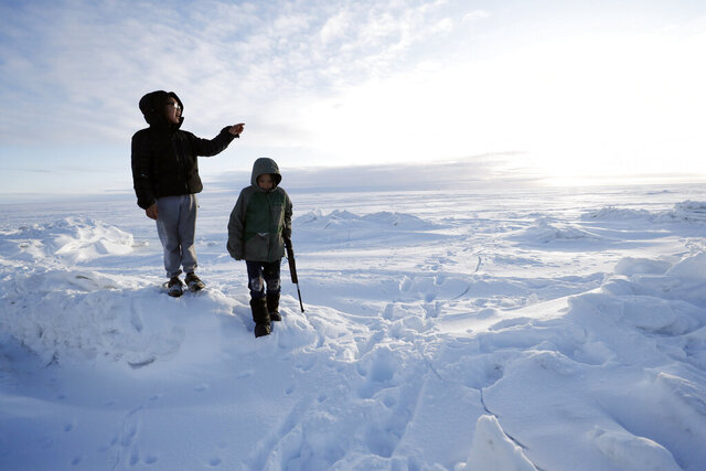 In this Saturday, Jan. 18, 2020, photo, George Chakuchin, left, and Mick Chakuchin look out over the Bering Sea near Toksook Bay, Alaska. The first Americans to be counted in the 2020 Census starting Tuesday, Jan. 21, live in this Bering Sea coastal village. The Census traditionally begins earlier in Alaska than the rest of the nation because frozen ground allows easier access for Census workers, and rural Alaska will scatter with the spring thaw to traditional hunting and fishing grounds. (AP Photo/Gregory Bull)