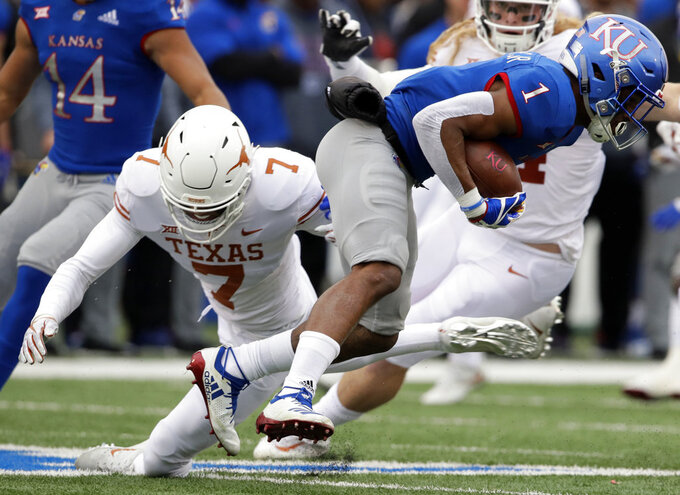 Kansas running back Pooka Williams Jr. (1) breaks a tackle by Texas defensive back Caden Sterns (7) during the first half of an NCAA college football game in Lawrence, Kan., Friday, Nov. 23, 2018. (AP Photo/Orlin Wagner)