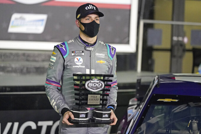 Alex Bowman holds the Pole Award Trophy in Victory Lane after winning the pole for the NASCAR Daytona 500 auto race at Daytona International Speedway, Wednesday, Feb. 10, 2021, in Daytona Beach, Fla. (AP Photo/John Raoux)