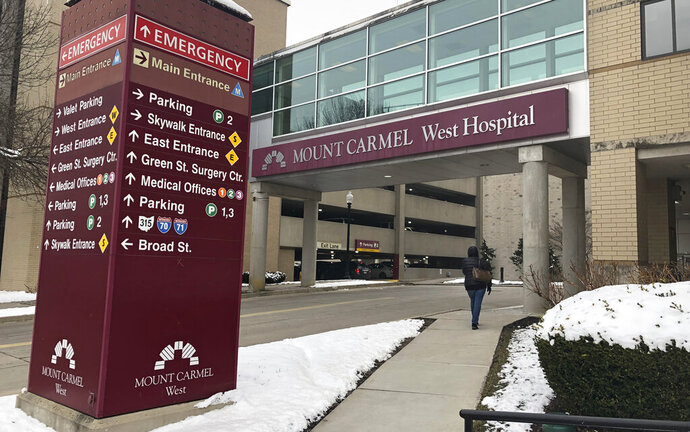 FILE - In this Jan. 15, 2019 file photo, the main entrance to Mount Carmel West Hospital is shown in Columbus, Ohio. The Mount Carmel Health System announced Thursday, July 11, 2019 that it's firing 23 more employees and changing leadership after investigating excessive painkiller doses given to dozens of patients who died. (AP Photo/Andrew Welsh Huggins, File)