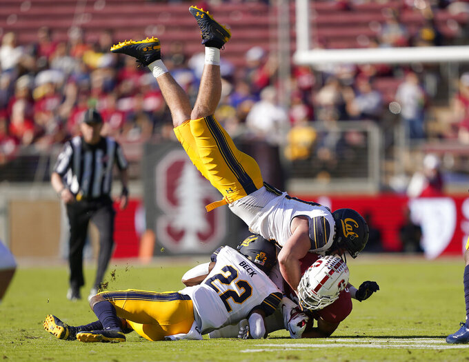 California linebacker Evan Weaver, top, and cornerback Traveon Beck (22) tackle Stanford wide receiver Osiris St. Brown (9) during the first half of an NCAA college football game Saturday, Nov. 23, 2019 in Stanford, Calif. (AP Photo/Tony Avelar)