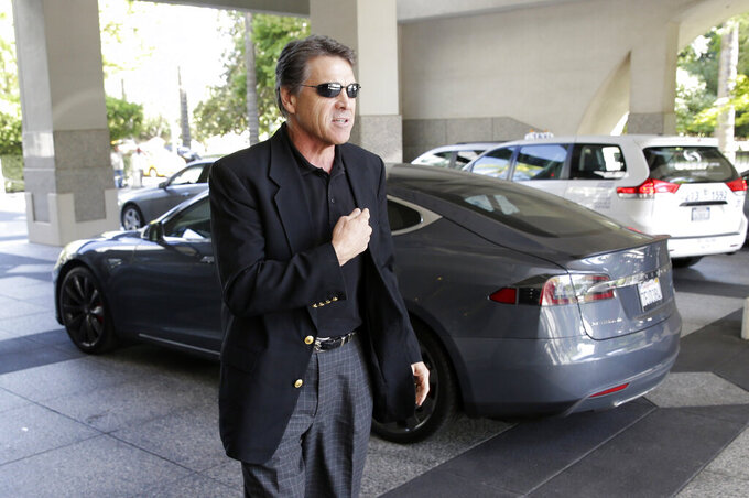 FILE -  In this June 10, 2014 file photo Texas Gov. Rick Perry walks over to talk to reporters after driving up in a Tesla Motors Type S electric car in Sacramento, Calif. Perry arrived at a meeting with statewide GOP lawmakers and officials across the street from the state Capitol to try to persuade California-based Tesla to build a plant in Texas. The two states have long been rivals. (AP Photo/Rich Pedroncelli, File)