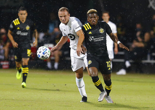 Minnesota United defender Chase Gasper (77) and Columbus Crew midfielder Luis Diaz (12) battle for the ball during the first half of an MLS soccer match in Kissimmee, Fla., Tuesday, July 28, 2020. (AP Photo/Reinhold Matay)