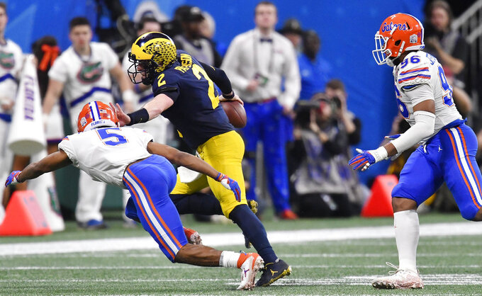 Michigan quarterback Shea Patterson (2) runs against Florida defensive back CJ Henderson (5) during the first half of the Peach Bowl NCAA college football game, Saturday, Dec. 29, 2018, in Atlanta. (AP Photo/Mike Stewart)