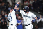Seattle Mariners' Mitch Haniger, right, is greeted by Ty France (23) after hitting a three-run home run against the Oakland Athletics in the fourth inning of a baseball game Monday, Sept. 27, 2021, in Seattle. (AP Photo/Elaine Thompson)