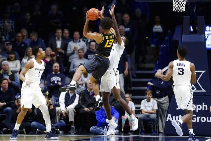 Missouri's Mark Smith (13) shoots next to Xavier's Naji Marshall, center right, during the first half of an NCAA college basketball game Tuesday, Nov. 12, 2019, in Cincinnati. (AP Photo/John Minchillo)
