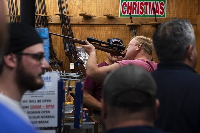 In this Friday, March 20, 2020, photo, a customer looks through a rifle scope as Bob's Little Sport Shop bustles with customers, in Glassboro, N.J. Gun retailers in New Jersey can remain open as essential businesses during the coronavirus outbreak. (Joe Lamberti/Camden Courier-Post via AP)