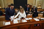 Committee staff lay out documents before a House Judiciary Committee markup of the articles of impeachment against President Donald Trump, Thursday, Dec. 12, 2019, on Capitol Hill in Washington. (AP Photo/Andrew Harnik)
