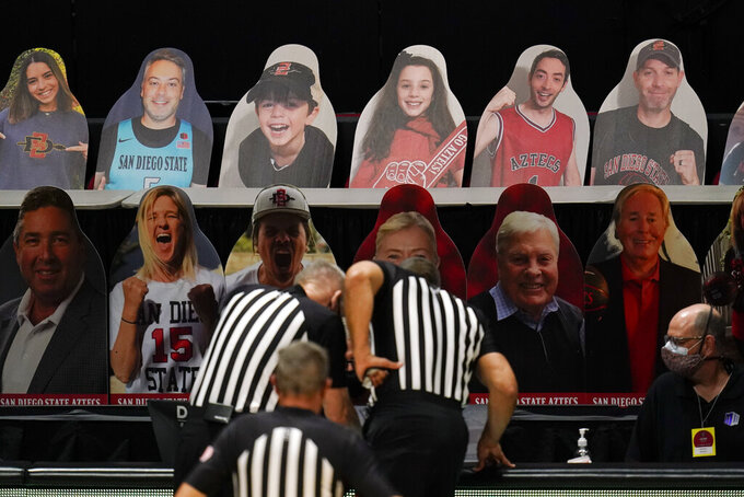 Cardboard cutouts of fans are displayed as officials determine how many seconds are left in the an NCAA college basketball game between boise State and San Diego State during the second half Thursday, Feb. 25, 2021, in San Diego. The game went into overtime. (AP Photo/Gregory Bull)