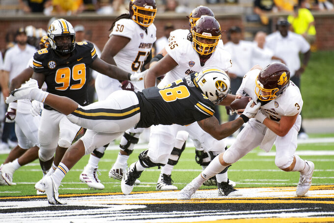 Central Michigan quarterback Jacob Sirmon, right, is sacked by Missouri's Mekhi Wingo, left, during the fourth quarter of an NCAA college football game Saturday, Sept. 4, 2021, in Columbia, Mo. (AP Photo/L.G. Patterson)