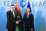 FILE - In this Dec. 4, 2018 file photo, Prime Minister of Libya Fayez al-Sarraj, left, is welcomed by EU foreign policy chief Federica Mogherini for a meeting in Brussels. Libya is on the verge of an all-out war involving a rogues' gallery of militias. The U.N. and Western nations support a transitional government set up in Tripoli in 2016 led by Sarraj, a technocrat with no military experience. His government was forced to court powerful militias for its own protection, and these groups have vowed to repel the forces of self-styled Libyan National Army, led by Field Marshal Khalifa Hifter, who launched a surprise offensive to retake Tripoli on April 5, 2019. (Stephanie Lecocq, Pool Photo via AP, File)