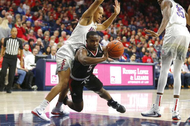 Omaha guard KJ Robinson (5) passes the ball in between Arizona guard Jemarl Baker Jr. and Christian Koloko (35) in the first half during an NCAA college basketball game, Wednesday, Dec. 11, 2019, in Tucson, Ariz. (AP Photo/Rick Scuteri)