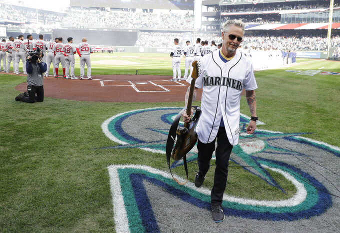 Pearl Jam guitarist Mike McCready carries his guitar after performing the national anthem before a baseball game between the Seattle Mariners and the Boston Red Sox, Thursday, March 28, 2019, in Seattle. (AP Photo/Ted S. Warren)