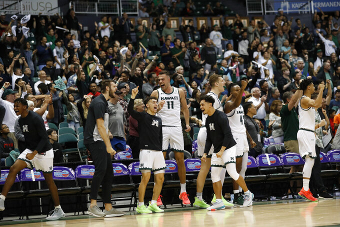 The Hawaii bench celebrates after defeating UTEP in an NCAA college basketball game Sunday, Dec. 22, 2019, in Honolulu. Hawaii defeated UTEP 67-63 advancing to the semifinals of the tournament. (AP Photo/Marco Garcia)