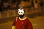 A protester wears a mask and marches on a street in Hong Kong Friday, Oct. 4, 2019. Thousands of defiant masked protesters have streamed into Hong Kong streets after the city's embattled leader invoked rarely used emergency powers to ban masks at rallies in a hardening of the government's stance after four months of anti-government demonstrations. Challenging the ban set to take effect Saturday, protesters crammed streets in the central business district and other areas, shouting