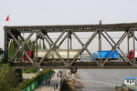 In this May 24, 2018, photo, trucks cross the friendship bridge connecting China and North Korea in the Chinese border town of Dandong, opposite side of the North Korean town of Sinuiju. China's imports from North Korea plunged 92.6 percent in June compared with a year earlier under U.N. sanctions imposed to stop Pyongyang's nuclear and missile programs, the customs agency said Friday, July 13, 2018. (Chinatopix Via AP)