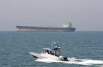 "FILE - In this July 2, 2012 file photo, an Iranian Revolutionary Guard speedboat moves in the Persian Gulf near an oil tanker. On Monday, April 8, 2019, the Trump administration designated Iran's Revolutionary Guard a ""foreign terrorist organization"" in an unprecedented move against a national armed force. Iran's Revolutionary Guard Corps went from being a domestic security force with origins in the 1979 Islamic Revolution to a transnational fighting force. (AP Photo/Vahid Salemi, File)"