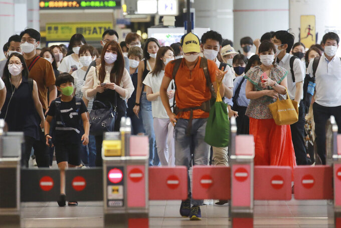 People wearing face masks to protect against the spread of the coronavirus walk at a train station in Tokyo, Wednesday, July 28, 2021. Tokyo Gov. Yuriko Koike on Wednesday urged younger people to cooperate with measures to bring down the high number of infections and get vaccinated, saying their activities are key to slowing the surge during the Olympics. (AP Photo/Koji Sasahara)