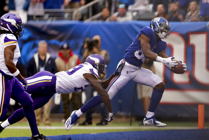 New York Giants wide receiver Darius Slayton (86) makes a touchdown catch against Minnesota Vikings cornerback Xavier Rhodes (29) during the second quarter of an NFL football game, Sunday, Oct. 6, 2019, in East Rutherford, N.J. (AP Photo/Adam Hunger)