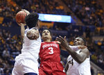 West Virginia guard Miles McBride, left, and forward Oscar Tshiebwe defend against Boston University guard Alex Vilarino (3) during the first half of an NCAA college basketball game Friday, Nov. 22, 2019, in Morgantown, W.Va. (AP Photo/Kathleen Batten)