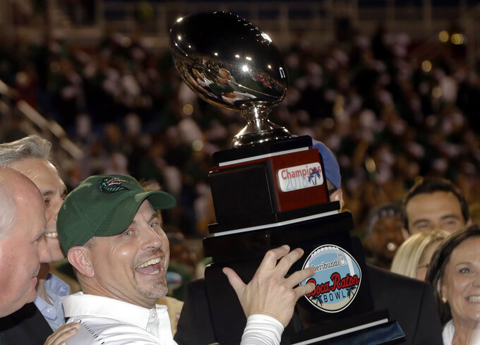 UAB head coach Bill Clark holds the trophy after winning the Boca Raton Bowl NCAA college football game against Northern Illinois, Tuesday, Dec. 18, 2018, in Boca Raton, Fla. UAB won 37-13. (AP Photo/Lynne Sladky)