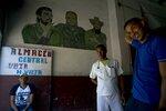 Men take a break inside a warehouse featuring a mural of revolutionary leaders Camilo Cienfuegos, right, Ernesto